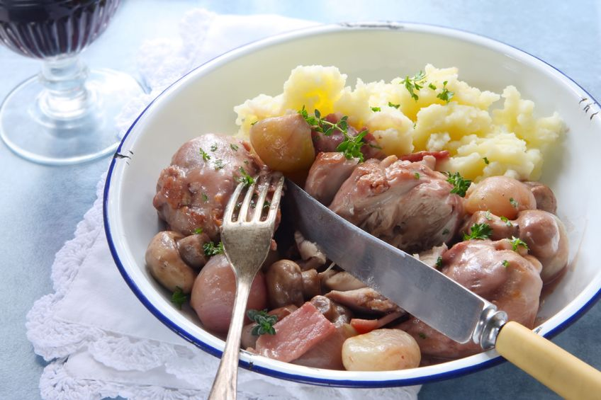 3161788 - coq au vin, in old enamel bowl, with lacy napkin and vintage cutlery.