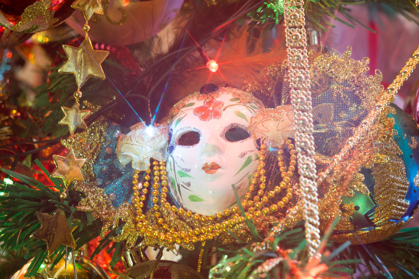 69568285 - carnival mask with feathers on a background of holiday lights.